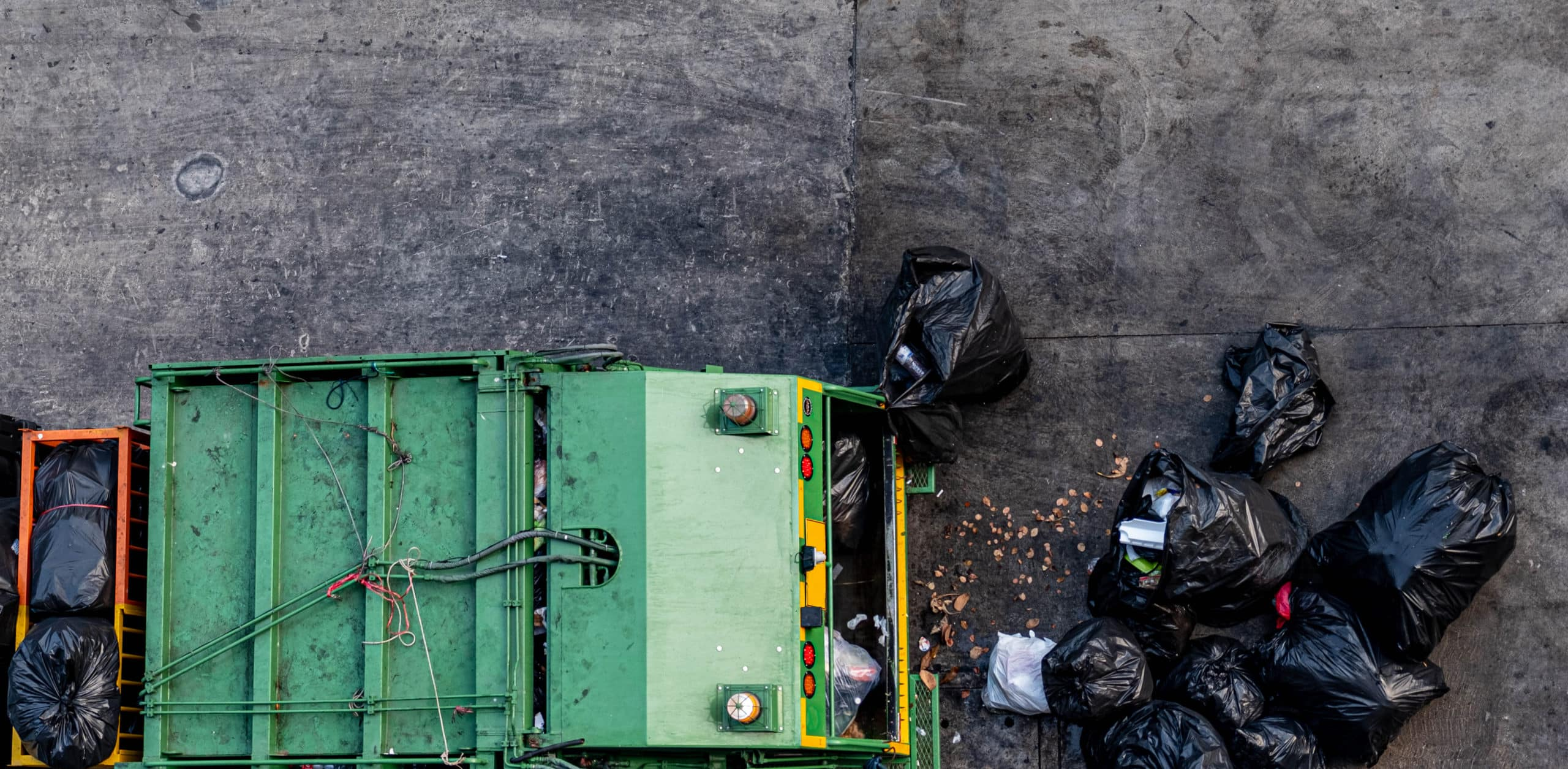 green-garbage-truck-collecting-large-number-black-garbage-bags